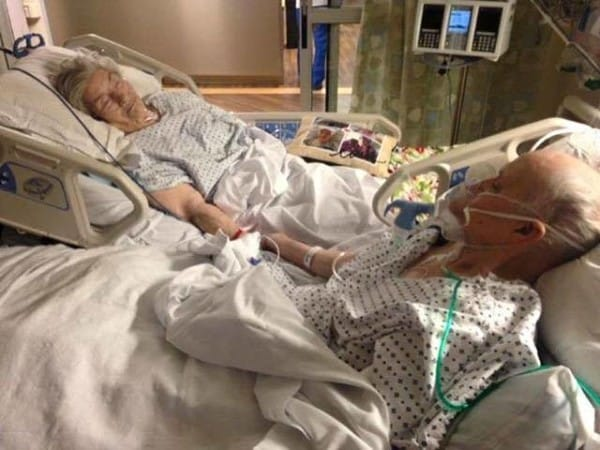 centenarian couple holds hand