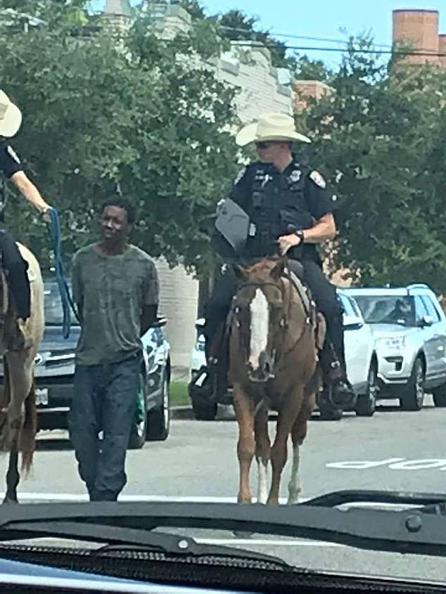 officers horseback lead handcuffed black man